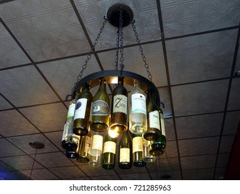 Knoxville, Tennessee, United States-July 8, 2017:  A chandelier comprising used wine bottles handing from a ceiling in a the Preservation Pub on Market Street.