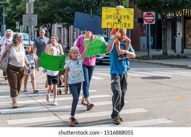 Knoxville, TN / USA - September 27, 2019: Climate Strike through Market Square and Krutch Park in downtown Knoxville Tennessee with people holding various signs to save the planet.