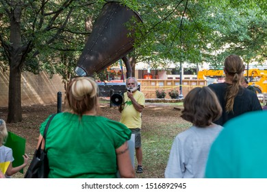 Knoxville, TN / USA - September 27, 2019: Climate Strike in downtown Knoxville, Tennessee, with a man in a yellow shirt holding a megaphone in front of a crowd of protesters