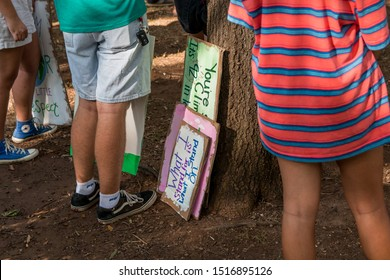 Knoxville, TN / USA - September 27, 2019: Climate Strike protest signs leaning against a tree at the start of the protest rally in Krutch Park in Knoxville, TN