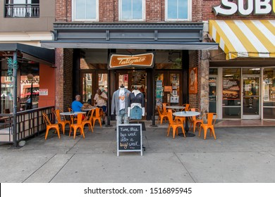 Knoxville, TN / USA - September 27, 2019: The Tailgate store in Market Square, Knoxville, TN, with a mannequin and sign out front with a background of orange.