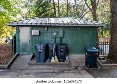Knoxville, TN / USA - September 27, 2019: Public maintenance building with trash cans and two brooms crossed against each other among the trees.