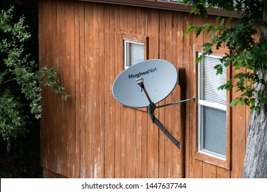 Knoxville, USA - June 2, 2019: Rustic vintage retro wooden house home building with windows in countryside and HughesNet Satellite Dish in Tennessee