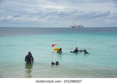 Ko Adang, Thailand - January 3, 2017:  Group of divers being trained near the shore with clipper boat at the horizon