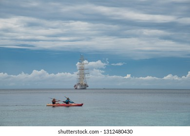 Ko Adang, Thailand - January 3, 2017:  Couple kayaking in front of Clipper Ship on horizon