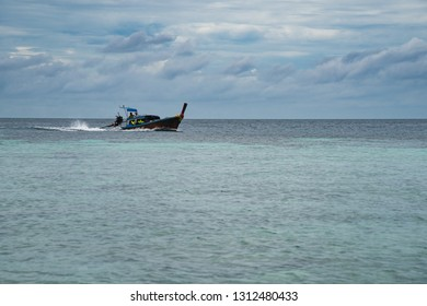 Ko Adang, Thailand - January 3, 2017:  Longtailed boat with turist running on the horizon