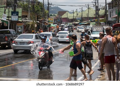 Ko Chang (Thailand) - April 13, 2018. People enjoy outdoor water splashing during hot summer day in the main road of Ko Chang Island, Trat Province, in Thailand's traditional New Year (Songkran).