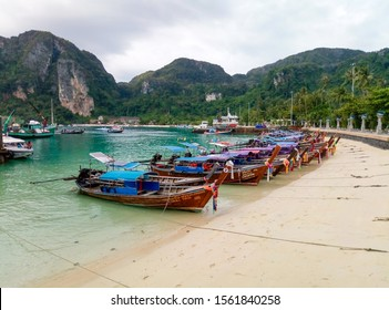 Ko phi phi, Krabi / Thailand - 01.30.2017: Traditional Thai fishing wooden boats wrapped with colored ribbons. At sand coast of tropical island.