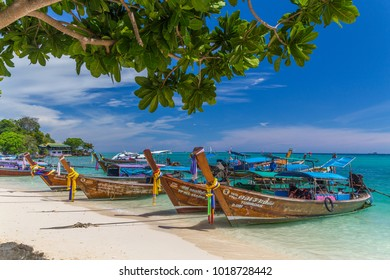 KO PHI PHI, THAILAND, 31ST MARCH 2017: Long-tail boats, the Andaman Sea and hills in Ko Phi Phi Don, South Thailand. Clear blue water can be seen.