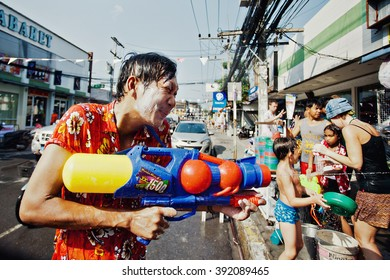 KO SAMUI, THAILAND - APRIL 13: Unidentified man shooting water in a water fight festival or Songkran Festival (Thai New Year) on April 13, 2014 in Chaweng Main Road, Ko Samui island, Thailand.