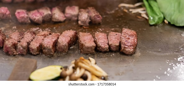 Kobe beef steak or high quality steak on hot plate pan during Teppanyaki Japanese Chef cooking and grilling in restaurant. Delicious and Popular for tourists attractions in Kobe district, Hyogo, Japan