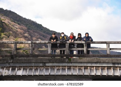 Kobe, Japan - 28 December 2016 : Unidentified happy family travel the Togetsukyo bridge across the Katsura river, at Arashiyama Kyoto Japan. Togetsukyo bridge with mountain dry tree background.