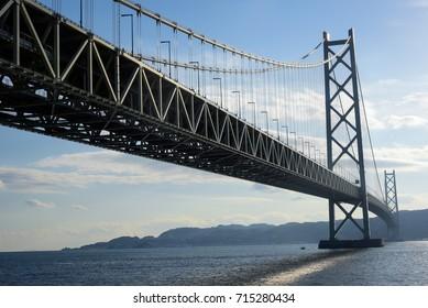 Kobe, Japan at Akashi Kaikyo Bridge in sunlight lens flair. The Akashi Kaikyo Bridge is, with a length of almost four kilometers, the world's longest