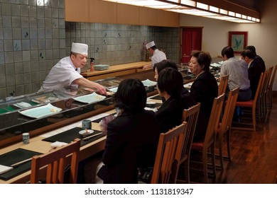 KOBE, JAPAN - APRIL 3, 2013: Japanese chef serves food in a restaurant in Kobe. Japanese restaurants often serve the food on a counter directly from the kitchen.