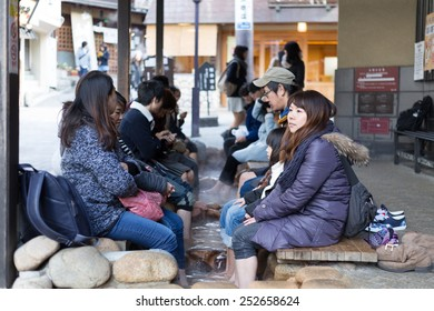 KOBE, JAPAN - FEBRUARY 14, 2015: Tourists enjoy a free foot bath (ashiyu) outside the larger of Arima Onsen's two public bath houses, Kin no Yu. Arima Onsen is one of Japan's three oldest hot springs.