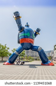 KOBE, JAPAN - JUNE 9, 2018: A giant red, blue, and metal steel statue of the Japanese robot manga character Gigantor (Tetsujin 28) in a karate pose stands in a public square.