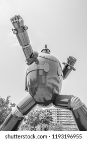 KOBE, JAPAN - JUNE 9, 2018: A black and white photo of a giant robot statue striking a karate pose in a park in Japan.