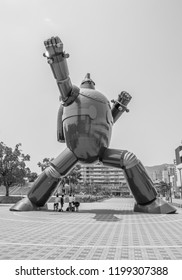 KOBE, JAPAN - JUNE 9, 2018: A black and white photo of a giant robot statue in a karate pose in a city park in Japan.