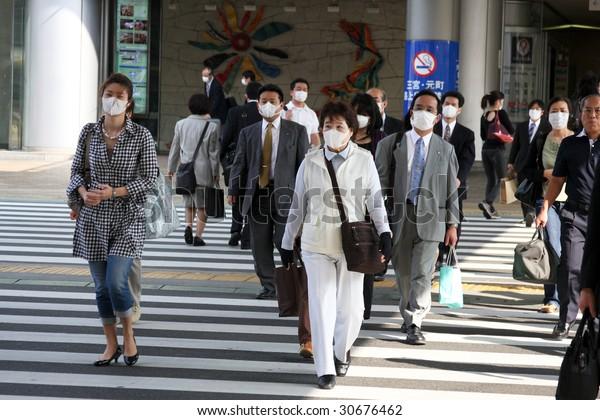 KOBE, JAPAN - MAY 20: People on the street wear face masks because of the outbreak of swine flu near Sannomiya JR station May 20, 2009 Kobe.