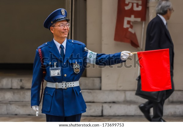 KOBE, JAPAN - NOVEMBER 17: Security Guard in Kobe, Japan on November 17, 2013. Unidentified security guard raises a red flag at a traffic lights for people to cross the street at Motomachi street