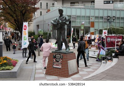 KOBE, JAPAN - NOVEMBER 23, 2016 : Unknown fans dancing at The Elvis Presley statue in Kobe Harborland. The statue had been in Harajuku, Tokyo since 1987 and it was moved to Kobe in 2009.