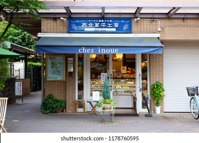 Kobe, JP - JUNE 11, 2017: The cute small bakery shop building facade with blue theme signboard, opens near the railway station.