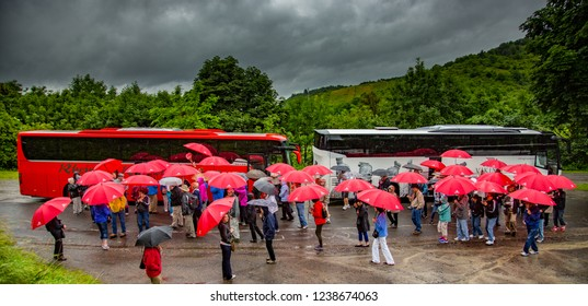 Koblenz, Germany - 7/15/2013:  A tour group with red umbrellas standing in the rain in Koblenz Germany preparing to board their bus.