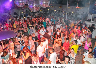 Koblevo, Ukraine July 15, 2011: Night club dj party people enjoy of music dancing sound with colorful light with Smoke Machine and lights show. Hands up in the earth.