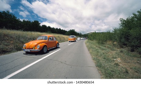 Kocani, Macedonia - 24 Jun, 2018: Volkswagon cars participating in VW event. Row of vintage German VWs buses and beetles driving on rural road on sunny day