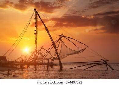 Kochi chinese fishnets on sunset. Fort Kochin, Kochi, Kerala, India. With lens flare and light leak