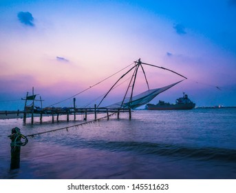 Kochi chinese fishnets and vessel on sunset  in Kerala. Fort Kochin,  South India