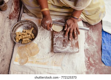 Kochi, India - December 11, 2015: Indian woman prepare traditional food on the street in Kerala. Delicious deep fried poori (puri) is indian bread