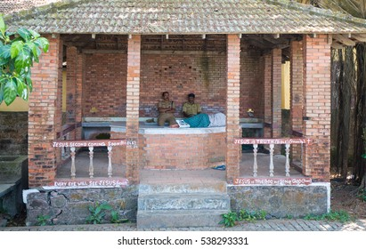KOCHI, INDIA - DECEMBER 16, 2016: Red brick Local police patrol post with two indian police officers and a sleeping man