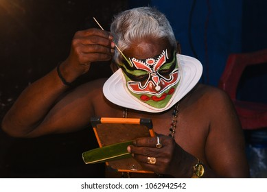 KOCHI, INDIA - FEBRUARY 10, 2017: Kathakali artist doing makeover at backstage for performing traditional dance drama folk art with face painting in temples of Kerala, India.