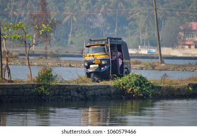 Kochi, India - February 21, 2018: An auto rickshaw traveling through a narrow road between backwaters.