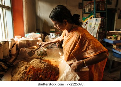 Kochi, India - January 16, 2016: Indian woman blending powder spices in the factory. Handmade work. Kerala famous for spices plantations.