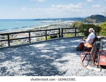 Kochi, Japan - April 7, 2018: Pilgrim taking a break and admiring the view of Kochi coastline at Zenjibuji, temple number 32 of Shikoku pilgrimage