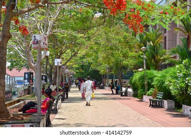 KOCHI, KERALA, INDIA, APRIL 30, 2016: Marine Drive - the picturesque promenade facing the backwaters. A favorite hangout for the locals and tourists. Man in traditional dress walking. Marine drive.