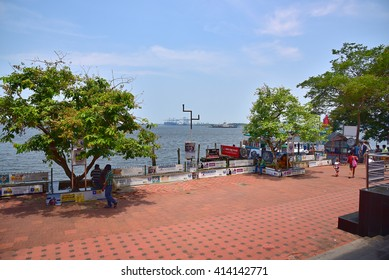 KOCHI, KERALA, INDIA, APRIL 30, 2016: Marine Drive - the picturesque promenade facing the backwaters. A favorite hangout for the locals and tourists. Scorching summer in Kerala. Ship in the port.