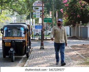 Kochi/India - December 24,2018 : A smiling Indian local man walking on the side walk with his auto rickshaw (three wheel) parking in the tourist city center area of Fort Kochi.