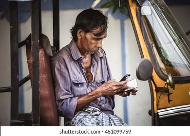 KOCHI/INDIA - NOVEMBER 22, 2015: Unidentified indian tuk-tuk driver looks at his mobile phone in  Kochi, India