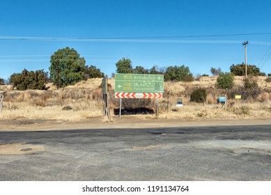 KOFFIEFONTEIN, SOUTH AFRICA, AUGUST 6, 2018: A directional sign near Koffiefontein in the Free State Province. Electricity infrastructure is visible