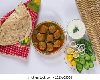 Kofta salan, Spicy indian curry, Delicious meatballs with salad, bread, yogurt and colourful cushion on white background.
