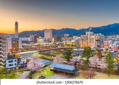 Kofu, Yamanashi, Japan downtown cityscape at dusk with spring foliage.