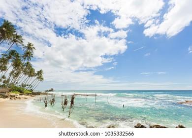 Koggala Beach, Sri Lanka, Asia - DECEMBER 2015 - Several native fishermen at Koggala Beach practicing their traditional way of stilt fishing