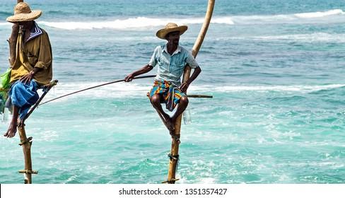 KOGGALA, Sri Lanka - February 09, 2016: Local traditional stilt fishermen rod in Indian ocean, Sri Lanka.