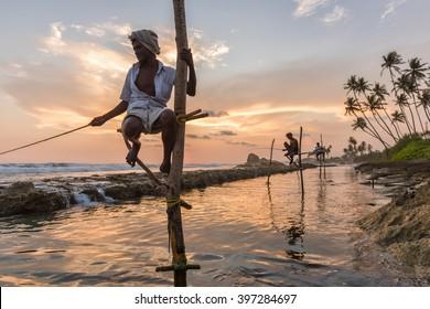 KOGGALA, SRI LANKA - MARCH 22, 2016: Local men fishing in traditional way. traditional fishermen at the sunset near Galle in Sri Lanka.