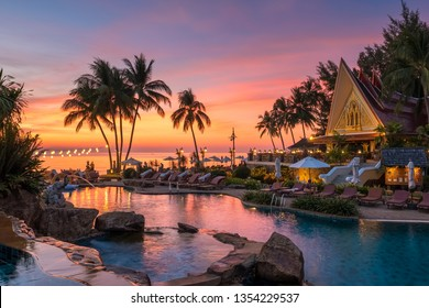 Koh Chang, Thailand - December 18, 2018: Beautiful sunset view with palm trees reflecting in swimming pool in luxury island resort in Thailand