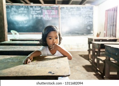 Koh Kong, Cambodia - SEPTEMBER 24, 2013: Cute a little khmer girl looking at camera while sitting at wooden desk in the classroom at elementary school. Koh Kong.