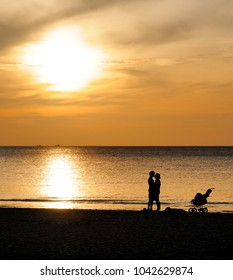Koh Lanta, Thailand - February 03, 2012. Happy young family with a baby carriage on the beach at sunset.